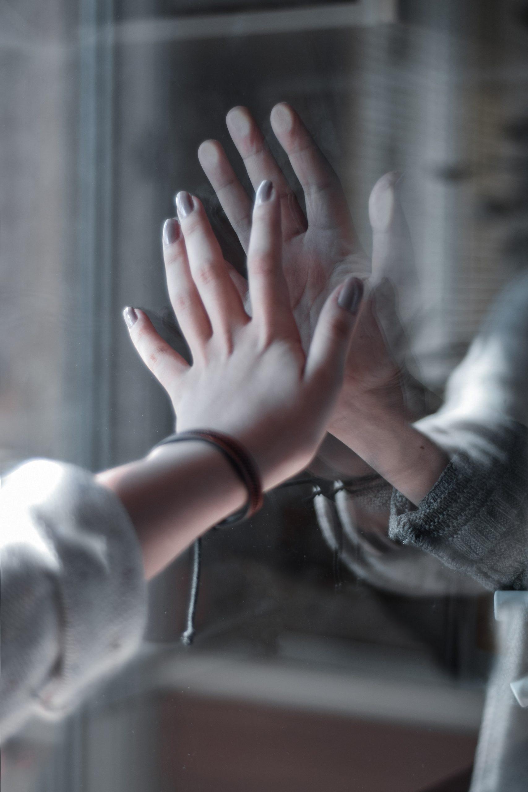 Deux mains séparées par une vitre